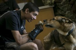 Army Spc. Alec Alcoser grins as he is reunited with his dog Alex at Audie L. Murphy Memorial VA Hospital, Friday, Sept. 14, 2018, in San Antonio, Texas. Alcoser was a military dog handler who suffered a traumatic brain injury and his dog lost a leg after they were hit by the blast of a suicide bomber in Afghanistan Aug. 5. Currently, Alcoser is receiving care at the VA's polytrauma unit, while Alex is rehabilitating at Joint Base San Antonio-Lackland. (Josie Norris/The San Antonio Express-News via AP)