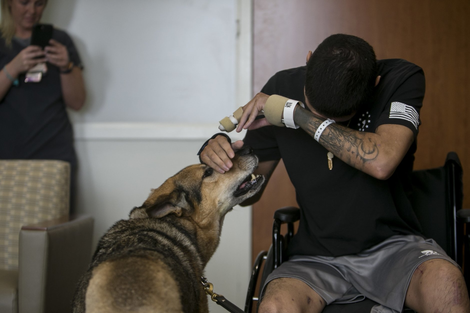 Army Spc. Alec Alcoser wipes away tears as he is reunited with his dog Alex at Audie L. Murphy Memorial VA Hospital, Friday, Sept. 14, 2018, in San Antonio, Texas. Alcoser was a military dog handler who suffered a traumatic brain injury and his dog lost a leg after they were hit by the blast of a suicide bomber in Afghanistan Aug. 5. Currently, Alcoser is receiving care at the VA's polytrauma unit, while Alex is rehabilitating at Joint Base San Antonio-Lackland.  (Josie Norris/The San Antonio Express-News via AP)