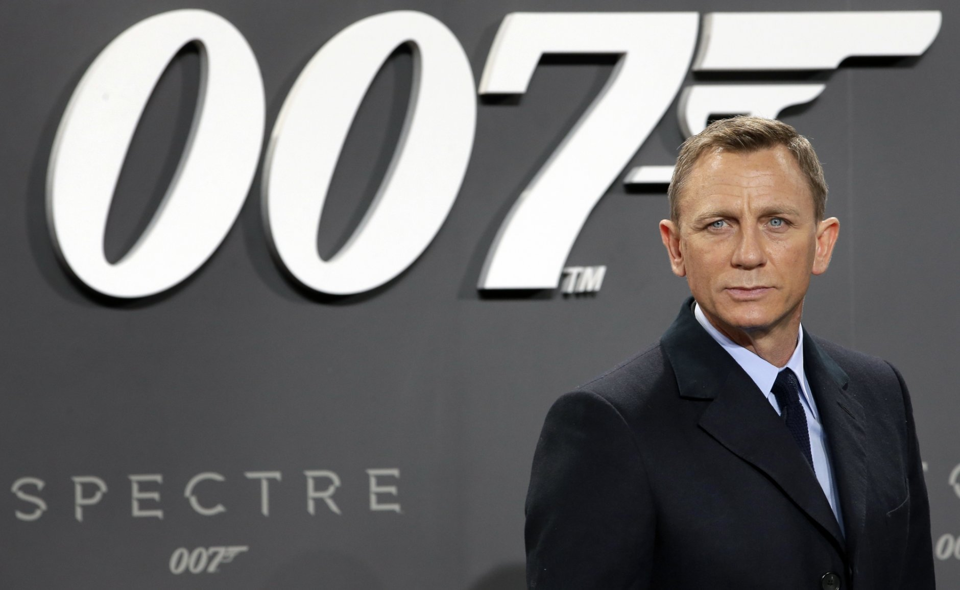 FILE - In this Oct. 28, 2015, file photo, actor Daniel Craig poses for the media as he arrives for the German premiere of the James Bond movie 'Spectre' in Berlin, Germany. Producers of the James Bond films say Cary Joji Fukunaga will direct the next instalment in the spy thriller series, replacing Danny Boyle. Michael G. Wilson, Barbara Broccoli and star Daniel Craig announced Thursday, Sept. 20, 2018 that the movie will start filming at London's Pinewood Studios on March 4, and will be released on Feb. 14, 2020.(AP Photo/Michael Sohn, File)