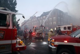 In this Sept. 19, 2018, photo, firefighters pour water on a fire at the Arthur Capper Senior Building, an apartment building that houses senior citizens. (AP Photo/Alex Brandon)
