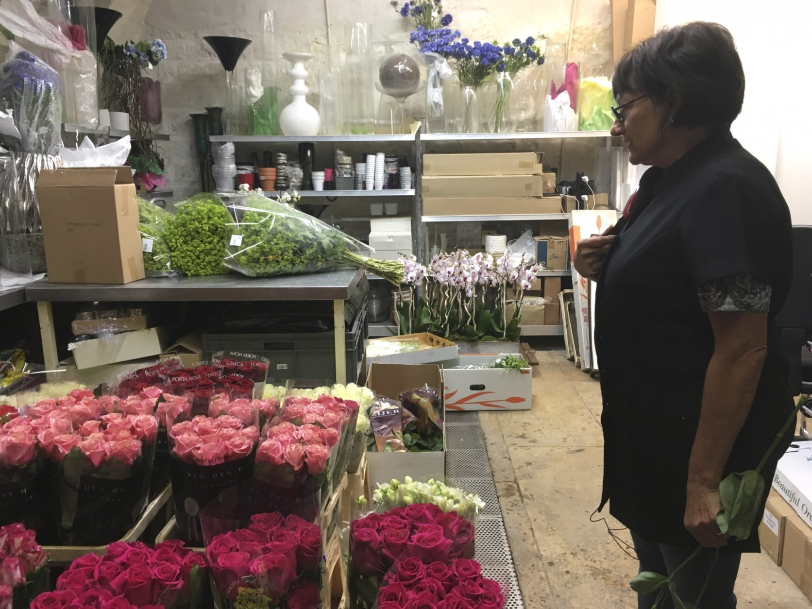 In this Thursday, Sept. 13, 2018 photo,  Marianne Fuseau, head florist, stands in the flower atelier at the Elysee presidential palace in Paris. The French president's wine cellar contains 14,000 bottles so precious that only a lucky few can enter it. Flower bouquets are displayed only for a couple of hours so they always look fresh. And the presidential chefs cook in 150-year-old pans. These and other behind-the-scenes quirks of the Elysee Palace are now getting a rare airing. (AP Photo/Sylvie Corbet)