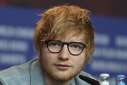 FILE - In this file photo dated Friday, Feb. 23, 2018, singer-songwriter Ed Sheeran speaks during a press conference for the film 'Songwriter' during the 68th edition of the International Film Festival Berlin, Berlinale, in Berlin, Germany.  International ticket reseller Viagogo said Tuesday Sept. 4, 2018, it's suing Ed Sheeran's promoter Stuart Galbraith and his company for fraud on allegations the company confiscated genuine tickets from concert-goers on Sheeran's recent 2017 tour, and forced them to purchase new tickets. (AP Photo/Markus Schreiber, FILE)