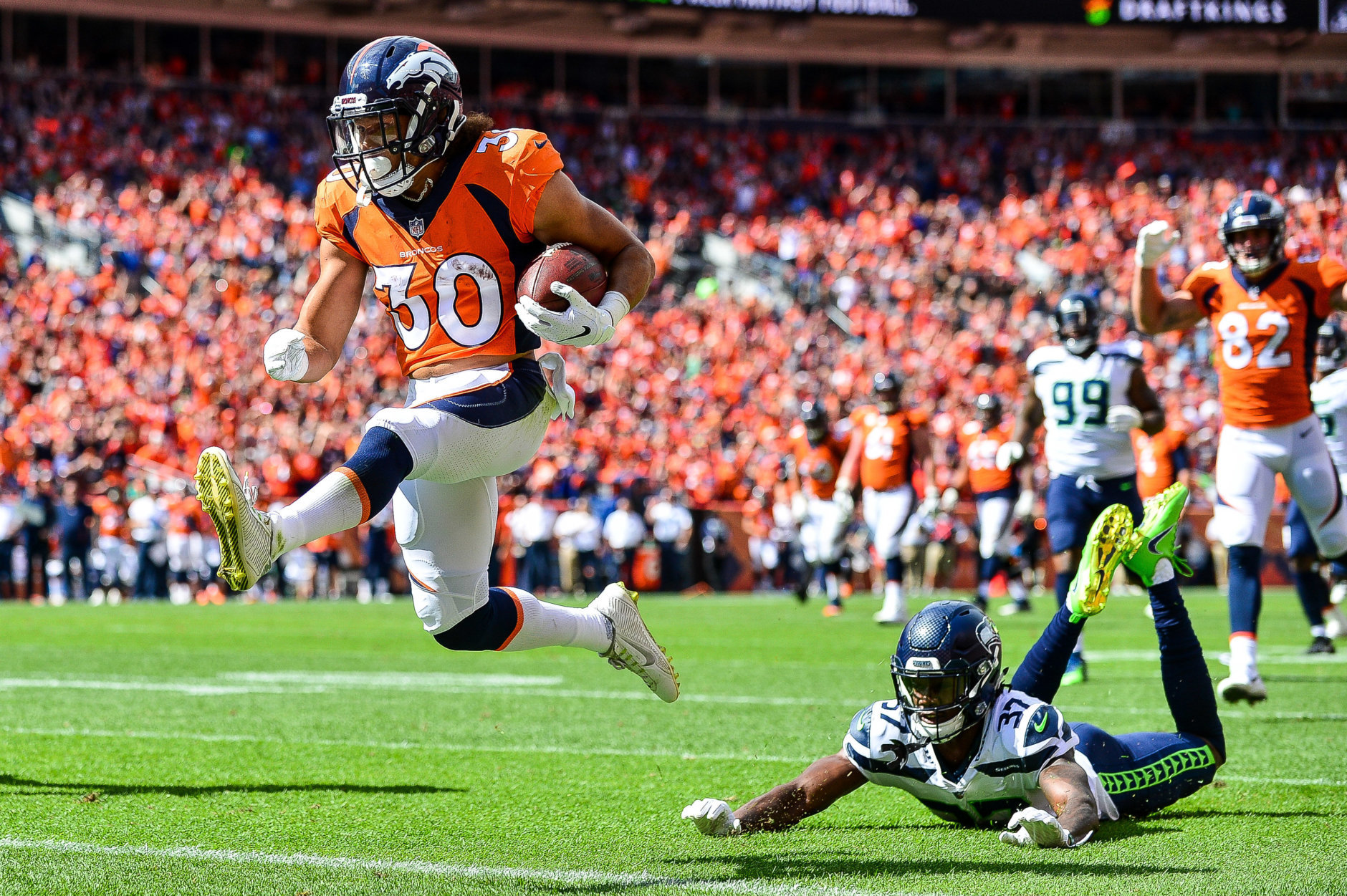 DENVER, CO - SEPTEMBER 9:  Running back Phillip Lindsay #30 of the Denver Broncos scores a first quarter touchdown on a reception as cornerback Tre Flowers #37 of the Seattle Seahawks falls to the ground during a game at Broncos Stadium at Mile High on September 9, 2018 in Denver, Colorado. (Photo by Dustin Bradford/Getty Images)