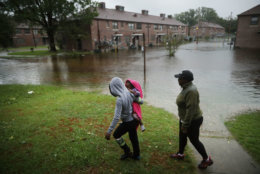 NEW BERN, NC - SEPTEMBER 13:  Diamond Dillahunt, 2-year-old Ta-Layah Koonce and Shkoel Collins survey the flooding at the Trent Court public housing apartments after the Neuse River topped its banks during Hurricane Florence September 13, 2018 in New Bern, United States. Coastal cities in North Carolina, South Carolina and Virginia are under evacuation orders as the Category 2 hurricane approaches the United States.  (Photo by Chip Somodevilla/Getty Images)
