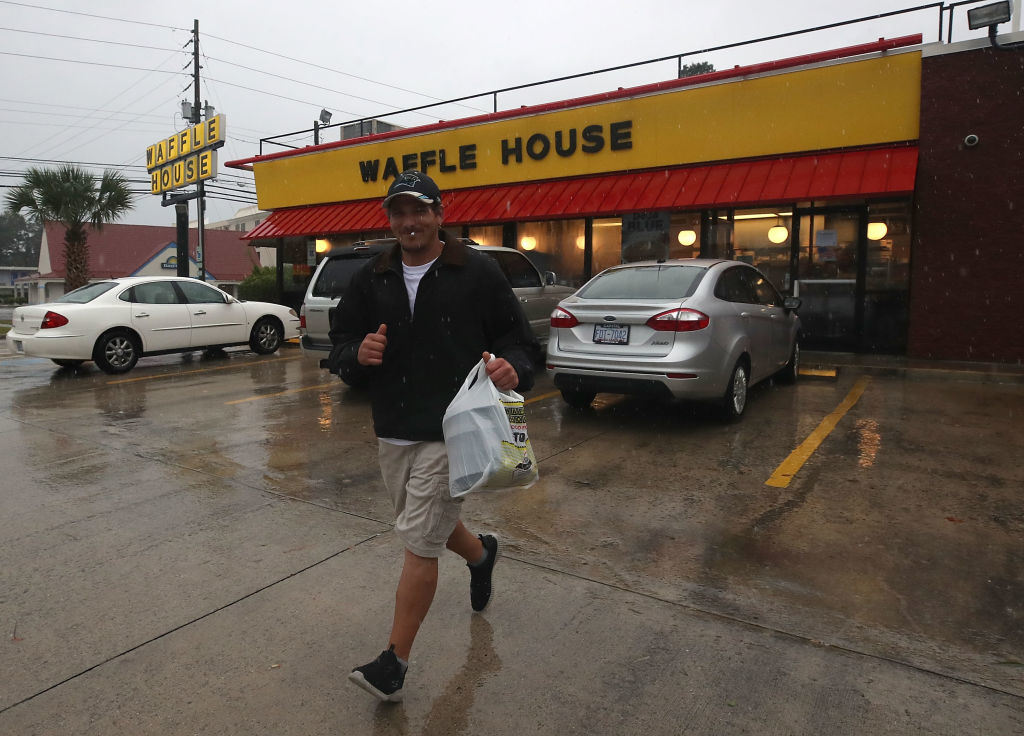 WILMINGTON, NC - SEPTEMBER 13: Josh Honeycutt runs to his car after picking up food at Waffle House, as the effects of Hurricane Florence start to hit the area, on September 13, 2018 in Wilmington, North Carolina. Hurricane Florence is expected on early Friday as a possible category 2 storm along the North Carolina and South Carolina coastline.  (Photo by Mark Wilson/Getty Images)