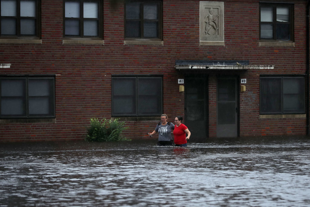 NEW BERN, NC - SEPTEMBER 13:  Residents wade through deep floodwater to retrieve belongings from the Trent Court public housing apartments after the Neuse River went over its banks during Hurricane Florence September 13, 2018 in New Bern, United States. Coastal cities in North Carolina, South Carolina and Virginia are under evacuation orders as the Category 2 hurricane approaches the United States.  (Photo by Chip Somodevilla/Getty Images)