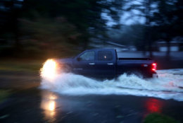 RIVER BEND, NC - SEPTEMBER 13:  A truck drives through deep water after the Neuse River went over its banks and flooded the street during Hurricane Florence September 13, 2018 in River Bend, North Carolina. Some parts of New Bern could be flooded with a possible 9-foot storm surge as the Category 2 hurricane approaches the United States.  (Photo by Chip Somodevilla/Getty Images)