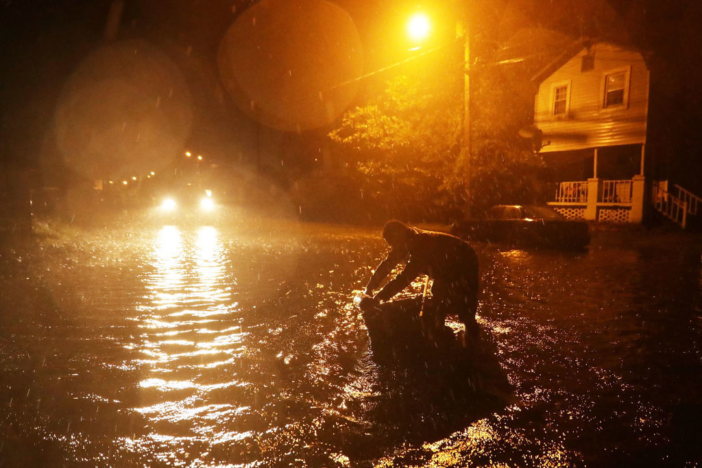 Residents walk in flooded streets in the historic downtown area as the Neuse River begins to flood its banks during Hurricane Florence September 13, 2018 in New Bern, United States. Coastal cities in North Carolina, South Carolina and Virgnia are under evacuation orders as the Category 2 hurricane approaches the United States.