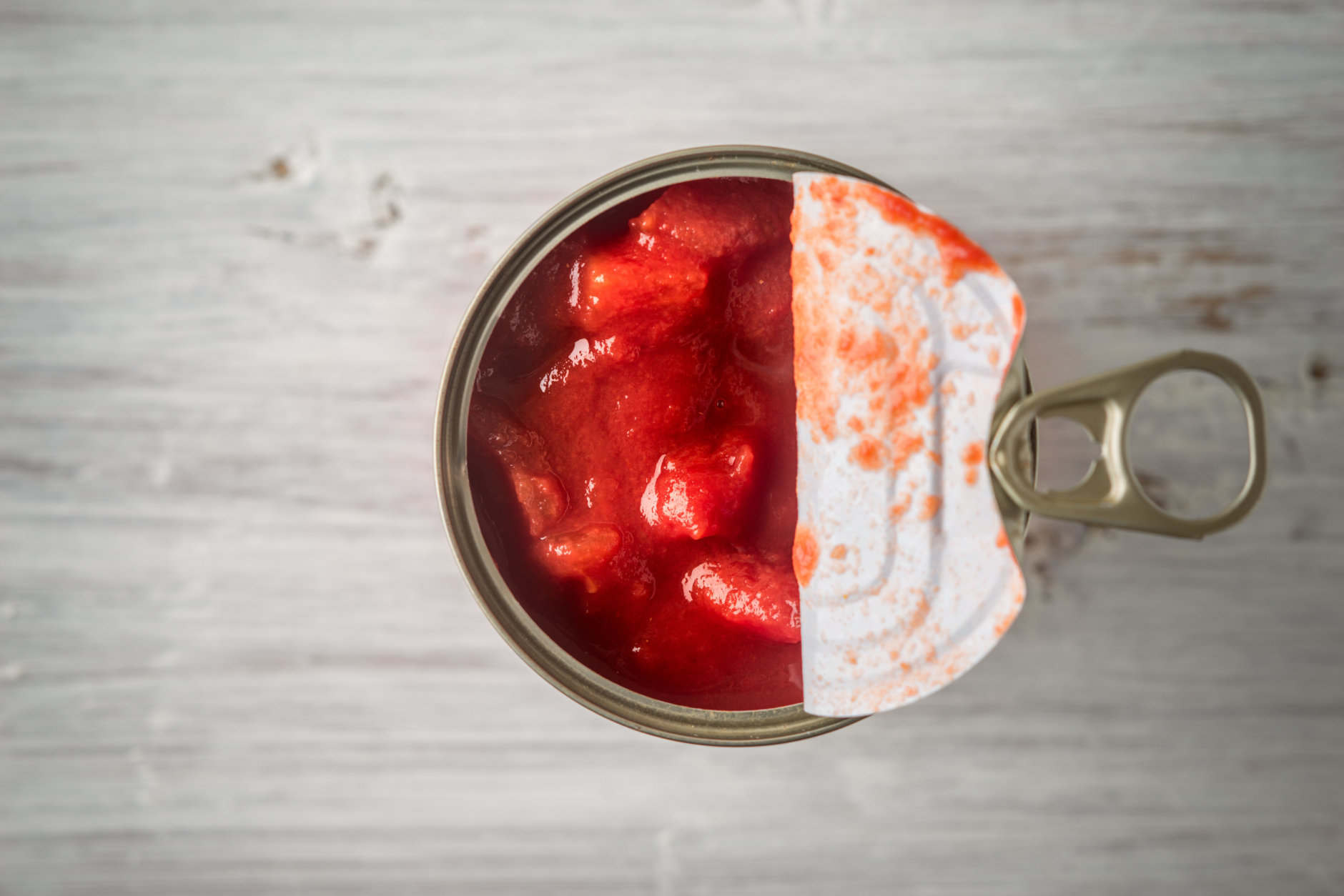 Chopped tomatoes in the metal can in the white wooden table top view horizontal