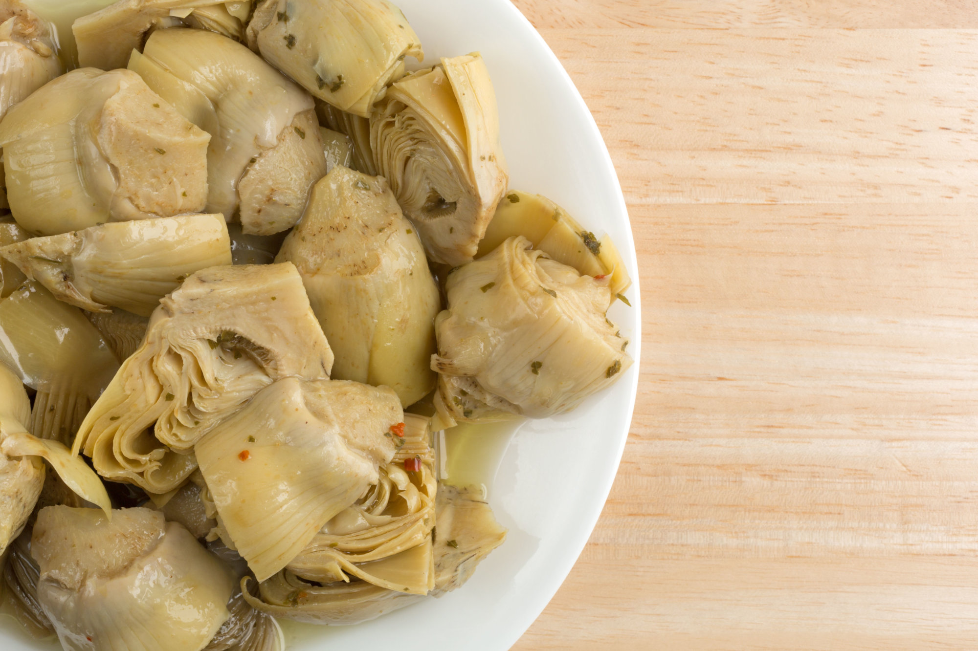 Top close view of marinated artichoke hearts on a  white plate atop a wood table.