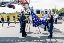 Members of the Annapolis Fire Department and the Naval District of Washington Fire Department Naval Academy Station work to put up the ladder arc flag. (Courtesy Megan Evans Photography)