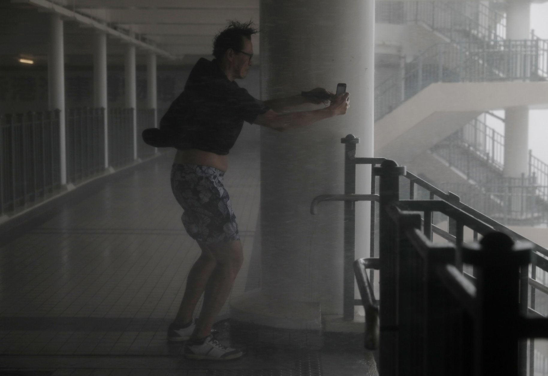 A man takes pictures against strong winds from Typhoon Mangkhut on the waterfront of Victoria Habour Hong Kong, Sunday, Sept. 16, 2018. Hong Kong and southern China hunkered down as strong winds and heavy rain from Typhoon Mangkhut lash the densely populated coast. The biggest storm of the year left at least 28 dead from landslides and drownings as it sliced through the northern Philippines. (AP Photo/Vincent Yu)