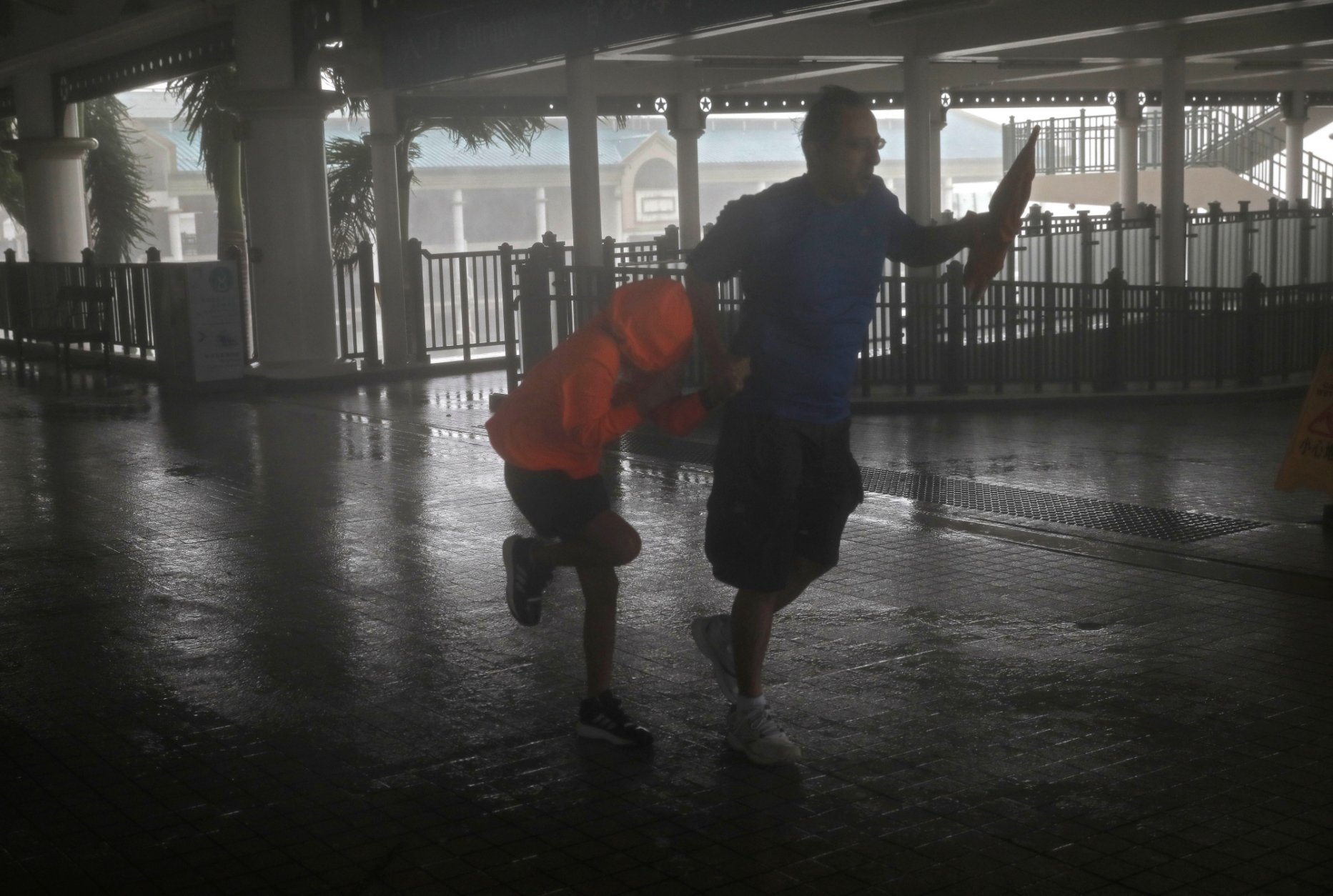 A man and a girl walk against strong winds from Typhoon Mangkhut on a pier on Victoria Habour Hong Kong, Sunday, Sept. 16, 2018. Hong Kong and southern China hunkered down as strong winds and heavy rain from Typhoon Mangkhut lash the densely populated coast. The biggest storm of the year left at least 28 dead from landslides and drownings as it sliced through the northern Philippines. (AP Photo/Vincent Yu)