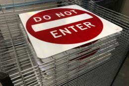 Screen-printed signs are placed on a rack to dry. (WTOP/Michelle Basch)