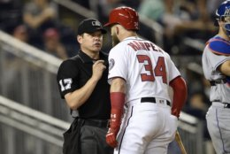 Washington Nationals' Bryce Harper (34), who had been called out on strikes, argues after he was ejected by home plate umpire D.J. Reyburn (17) during the 12th inning of a baseball game against the New York Mets, Thursday, Sept. 20, 2018, in Washington. The Mets won 5-4 in 12 innings. (AP Photo/Nick Wass)