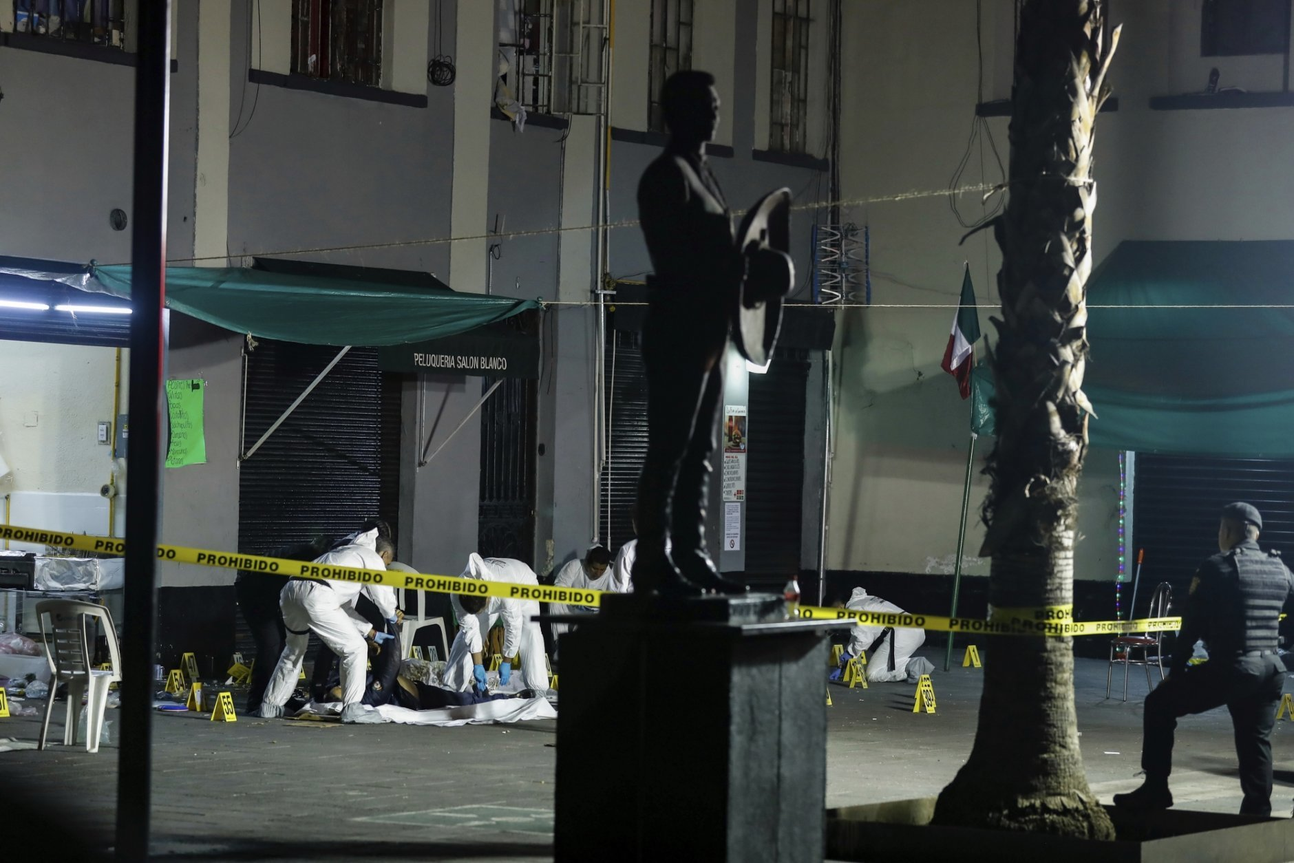 Crime scene workers cover the bodies of victims of a shooting in Garibaldi Plaza, in Mexico City, Friday Sept. 14, 2018. Mexican authorities say four people have been killed and nine wounded in a shooting at the capital's emblematic Garibaldi Plaza, a popular spot for tourists. (AP Photo/Stringer)