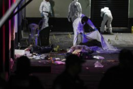 A crime scene worker covers up one of the bodies of victims of a shooting in Garibaldi Plaza, in Mexico City, Friday Sept. 14, 2018. Mexican authorities say four people have been killed and nine wounded in a shooting at the capital's emblematic Garibaldi Plaza, a popular spot for tourists. (AP Photo/Stringer)