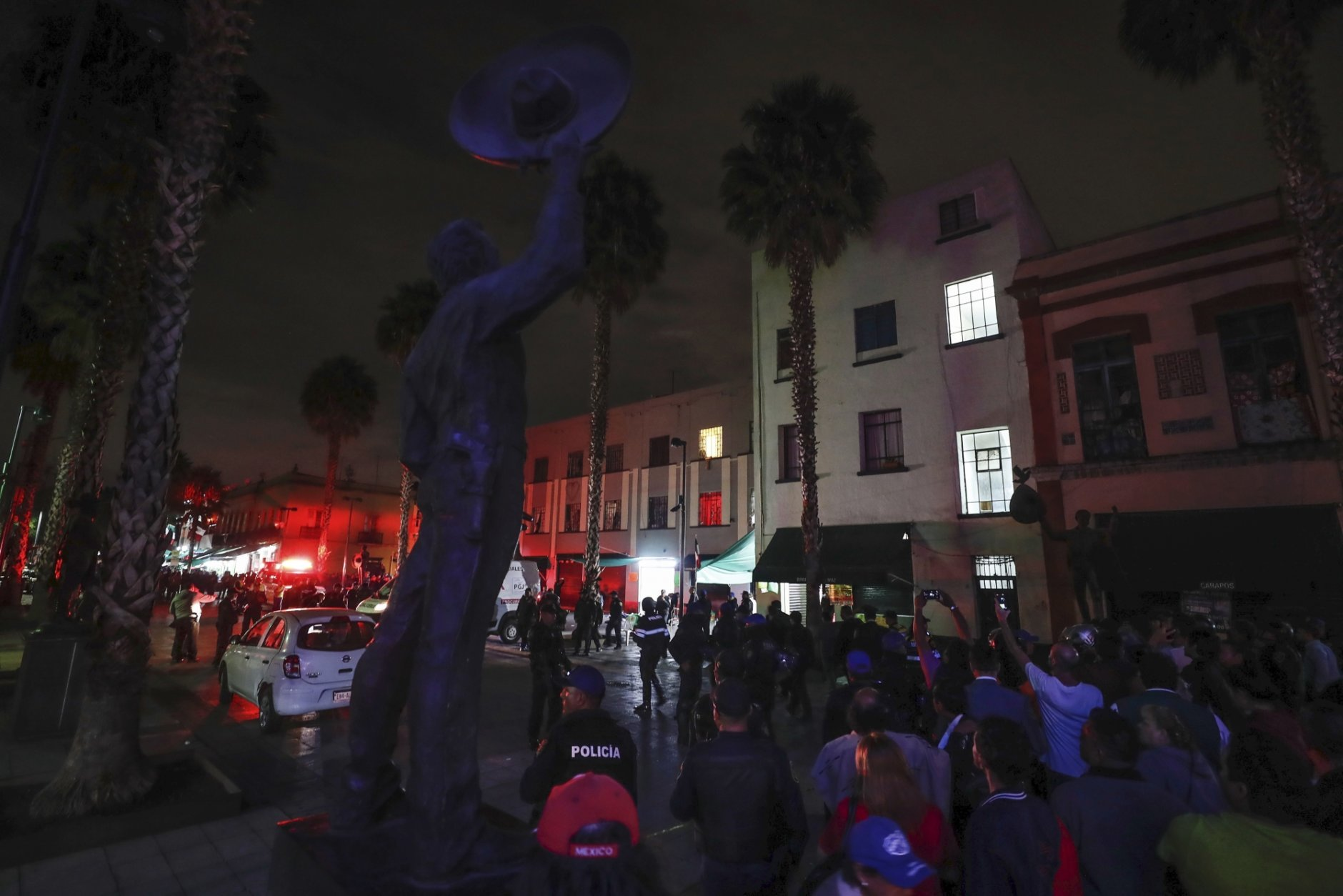 Curious onlookers gather on the perimeters of a crime scene after a shooting in Garibaldi Plaza in Mexico City, Friday, Sept. 14, 2018. Mexican authorities say at least four people have been killed and nine wounded in a shooting at the capital's emblematic plaza. (AP Photo/Stringer)