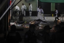 Forensic investigators examine the crime scene where authorities say at least four people have been killed and nine wounded in a shooting at Garibaldi Plaza, in Mexico City, Friday, Sept. 14, 2018.  Gunmen dressed as mariachis opened fired on an establishment in the capital's emblematic plaza, a spot popular for tourists. (AP Photo/Stringer)