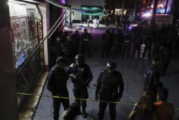 Police block access to a crime scene after a shooting in Plaza Garibaldi in Mexico City, Friday, Sept. 14, 2018. At least four individuals have died in a shooting in Plaza Garibaldi after three gunmen dressed as mariachis opened fired on an establishment that is believed to be a drug distribution point of a local gang. (AP Photo/Stringer)