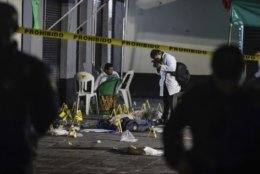 Forensic investigators document the crime scene where authorities say at least four people have been killed and nine wounded in a shooting at Garibaldi Plaza, in Mexico City, Friday, Sept. 14, 2018. Gunmen dressed as mariachis opened fired on an establishment in the capital's emblematic plaza, a spot popular for tourists. (AP Photo/Stringer)