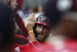 Washington Nationals' Bryce Harper celebrates in the dugout after his two-run home run against the Atlanta Braves during the first inning of a baseball game Sunday, Sept. 16, 2018, in Atlanta. (AP Photo/Tami Chappell)