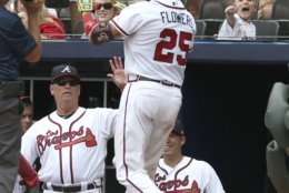 Atlanta Braves Tyler Flowers (25) is greeted at the dugout by manager Brian Snitker after a two-run home run against the Washington Nationals in the fourth inning of a baseball game Sunday, Sept. 16, 2018, in Atlanta. The Nationals defeated the Braves, 6-4. (AP Photo/Tami Chappell)