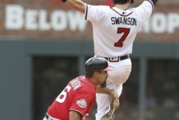 Washington Nationals runner Anthony Rendon (6) tries to break up a double play turned by Atlanta Braves Dansby Swanson (7) in the seventh inning of a baseball game Sunday, Sept. 16, 2018, in Atlanta. The Nationals defeated the Braves 6-4. (AP Photo/Tami Chappell)