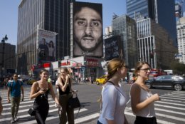 FILE - In this Sept. 6, 2018, file photo, people in New York walk past a Nike advertisement featuring former San Francisco 49ers quarterback Colin Kaepernick, known for kneeling during the national anthem to protest police brutality and racial inequality. In response to Nike's support of Kaepernick, the Rhode Island town of North Smithfield is considering asking its departments to refrain from purchasing Nike products. (AP Photo/Mark Lennihan, File)