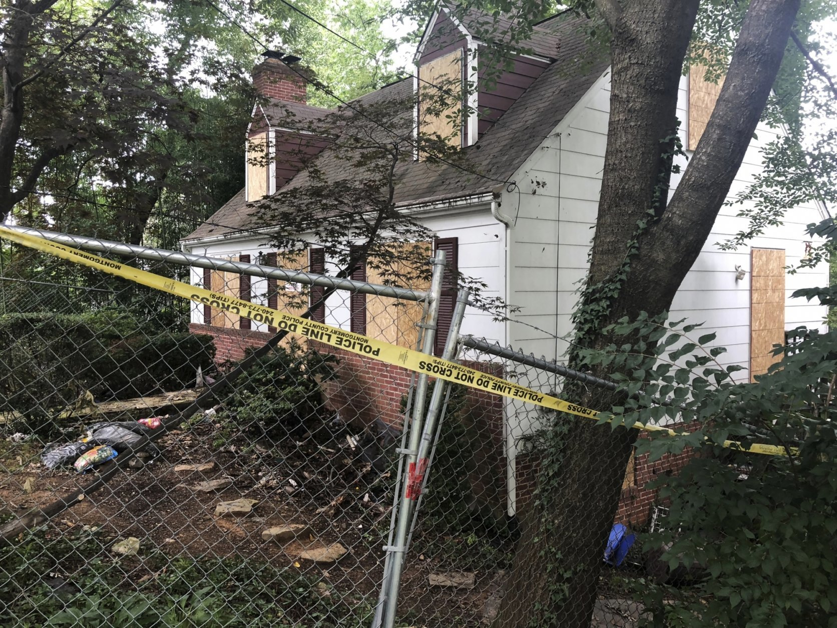 In this Aug. 18, 2018, photo, police tape surrounds the house where Askia Khafra died in a fire while digging underground tunnels for a secretive campaign to build a nuclear bunker in Bethesda, Md. (AP Photo/Michael Kunzelman)