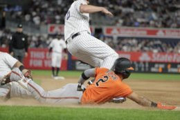 Baltimore Orioles' Jonathan Villar (2) slides to first base for a single during the tenth inning of a baseball game against the New York Yankees Saturday, Sept. 22, 2018, in New York. (AP Photo/Frank Franklin II)