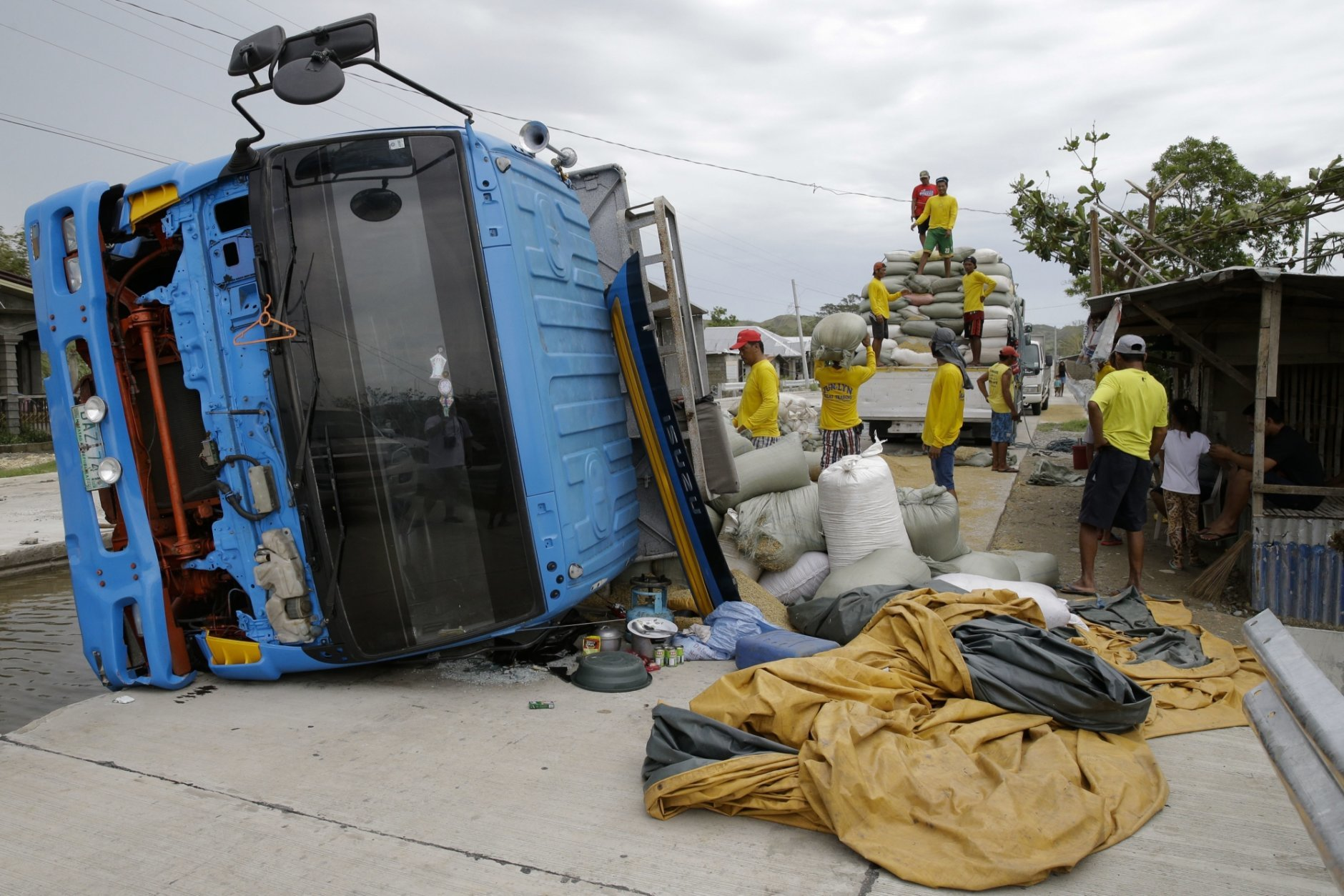 Workers carry sacks of grains from a toppled truck in Cagayan province, northeastern Philippines on Sunday, Sept. 16, 2018. Driver Alvin Buelta said his truck fell after he failed to see the road repairs due to the high floods caused by Typhoon Mangkhut on Friday night. The typhoon roared toward densely populated Hong Kong and southern China on Sunday after ravaging across the northern Philippines with ferocious winds and heavy rain causing landslides and collapsed houses. (AP Photo/Aaron Favila)