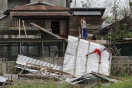 Residents work to repair a damaged roof due to strong winds from Typhoon Mangkhut after it barreled across Tuguegarao city in Cagayan province, northeastern Philippines on Sunday, Sept. 16, 2018. Typhoon Mangkhut roared toward densely populated Hong Kong and southern China on Sunday after ravaging across the northern Philippines with ferocious winds and heavy rain causing landslides and collapsed houses. (AP Photo/Aaron Favila)
