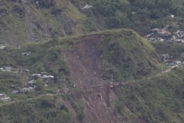 A helicopter passes by the site of a landslide where victims are believed to have been buried after Typhoon Mangkhut barreled across Itogon, Benguet province, northern Philippines, Monday, Sept. 17, 2018. Itogon Mayor Victorio Palangdan said that at the height of the typhoon's onslaught Saturday afternoon, dozens of people, mostly miners and their families, rushed into an old three-story building in the village of Ucab. The building, a former mining bunkhouse that had been transformed into a chapel, was obliterated when part of a mountain slope collapsed. (AP Photo/Aaron Favila)