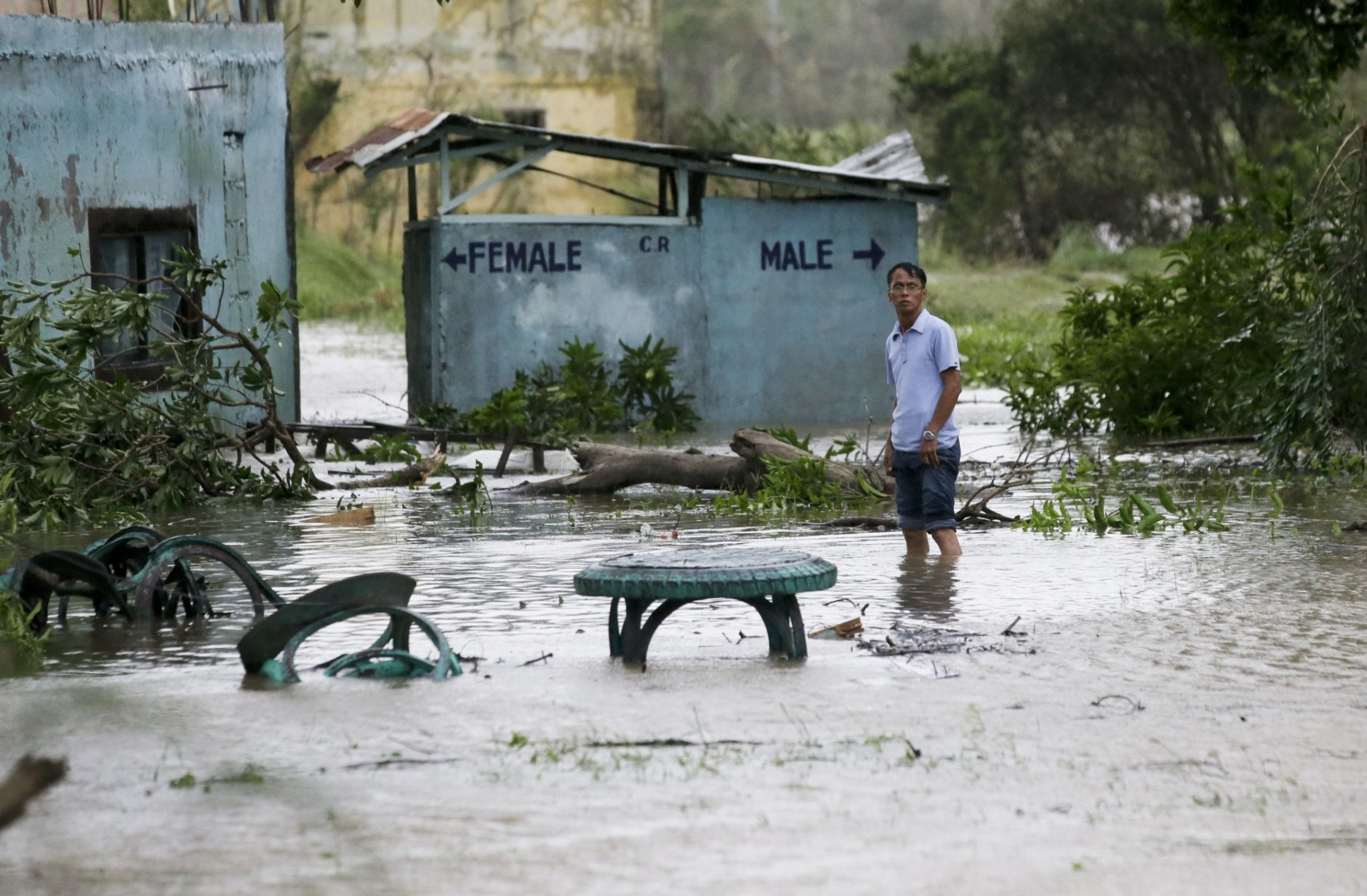 A resident wades along a flooded area as Typhoon Mangkhut barreled across Tuguegarao city in Cagayan province, northeastern Philippines on Saturday, Sept. 15, 2018. The typhoon slammed into the Philippines northeastern coast early Saturday, it's ferocious winds and blinding rain ripping off tin roof sheets and knocking out power, and plowed through the agricultural region at the start of the onslaught. (AP Photo/Aaron Favila)