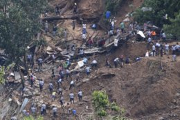 Rescuers work on the site where victims were believed to have been buried by a landslide after Typhoon Mangkhut barreled across Itogon, Benguet province, northern Philippines, Monday, Sept. 17, 2018. Itogon Mayor Victorio Palangdan said that at the height of the typhoon's onslaught Saturday afternoon, dozens of people, mostly miners and their families, rushed into an old three-story building in the village of Ucab. The building, a former mining bunkhouse that had been transformed into a chapel, was obliterated when part of a mountain slope collapsed. (AP Photo/Aaron Favila)