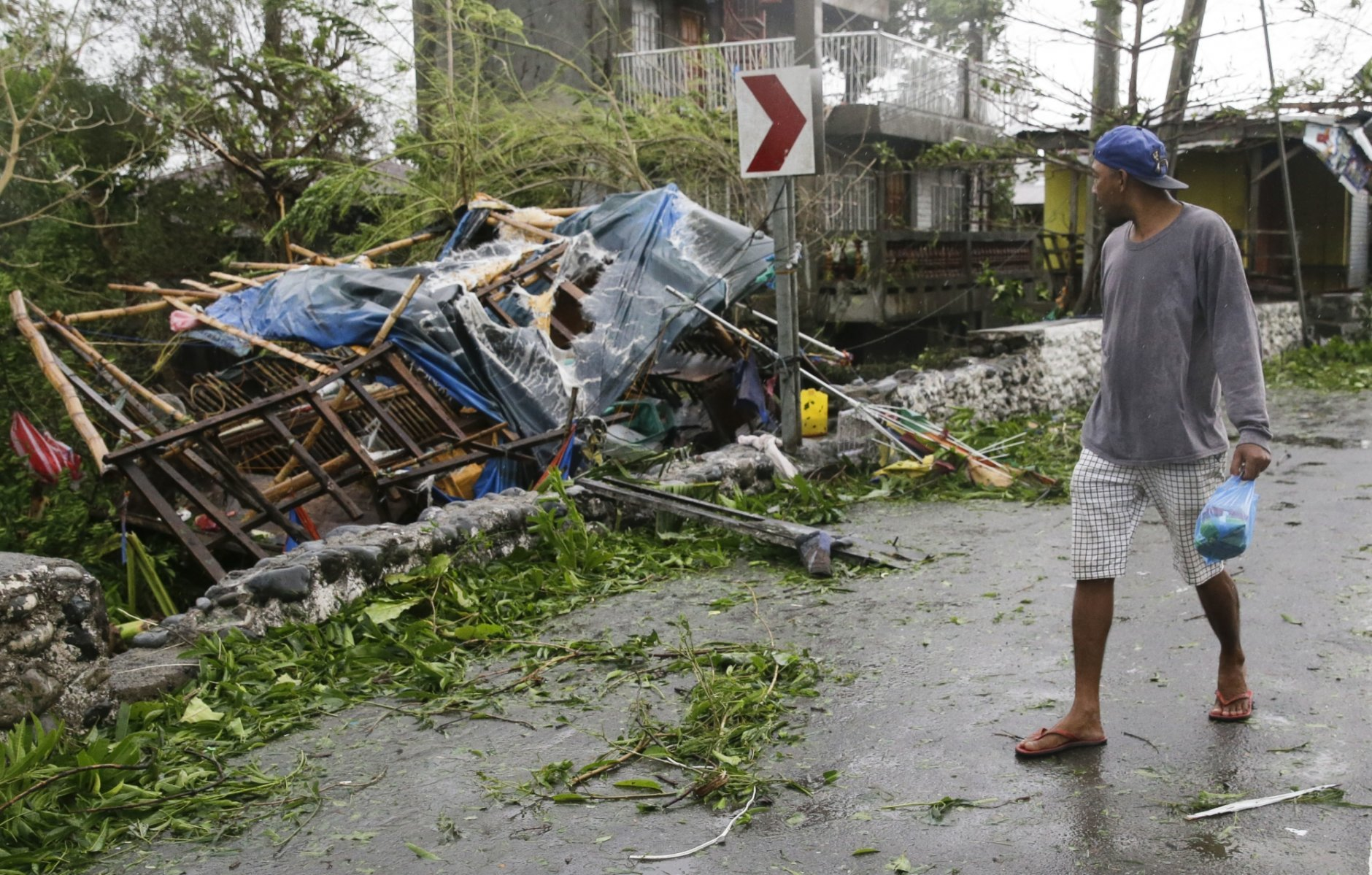 A man looks at a damaged house due to strong winds from Typhoon Mangkhut as it barreled across Tuguegarao city in Cagayan province, northeastern Philippines on Saturday, Sept. 15, 2018. The typhoon slammed into the Philippines northeastern coast early Saturday, it's ferocious winds and blinding rain ripping off tin roof sheets and knocking out power, and plowed through the agricultural region at the start of the onslaught. (AP Photo/Aaron Favila)