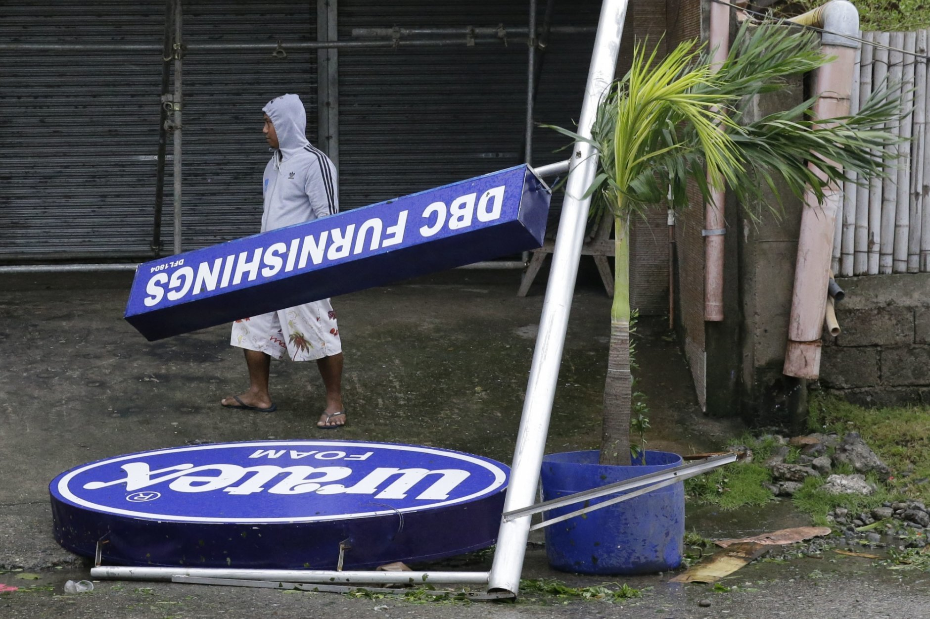 A resident walks beside a sign toppled by strong winds from Typhoon Mangkhut as it barreled across Tuguegarao city in Cagayan province, northeastern Philippines on Saturday, Sept. 15, 2018. The typhoon slammed into the Philippines northeastern coast early Saturday, it's ferocious winds and blinding rain ripping off tin roof sheets and knocking out power, and plowed through the agricultural region at the start of the onslaught. (AP Photo/Aaron Favila)