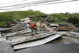 A Filipino government worker picks up pieces from a structure destroyed by strong winds from Typhoon Mangkhut as it barreled across Tuguegarao city in Cagayan province, northeastern Philippines on Saturday, Sept. 15, 2018. The typhoon slammed into the Philippines northeastern coast early Saturday, it's ferocious winds and blinding rain ripping off tin roof sheets and knocking out power, and plowed through the agricultural region at the start of the onslaught. (AP Photo/Aaron Favila)