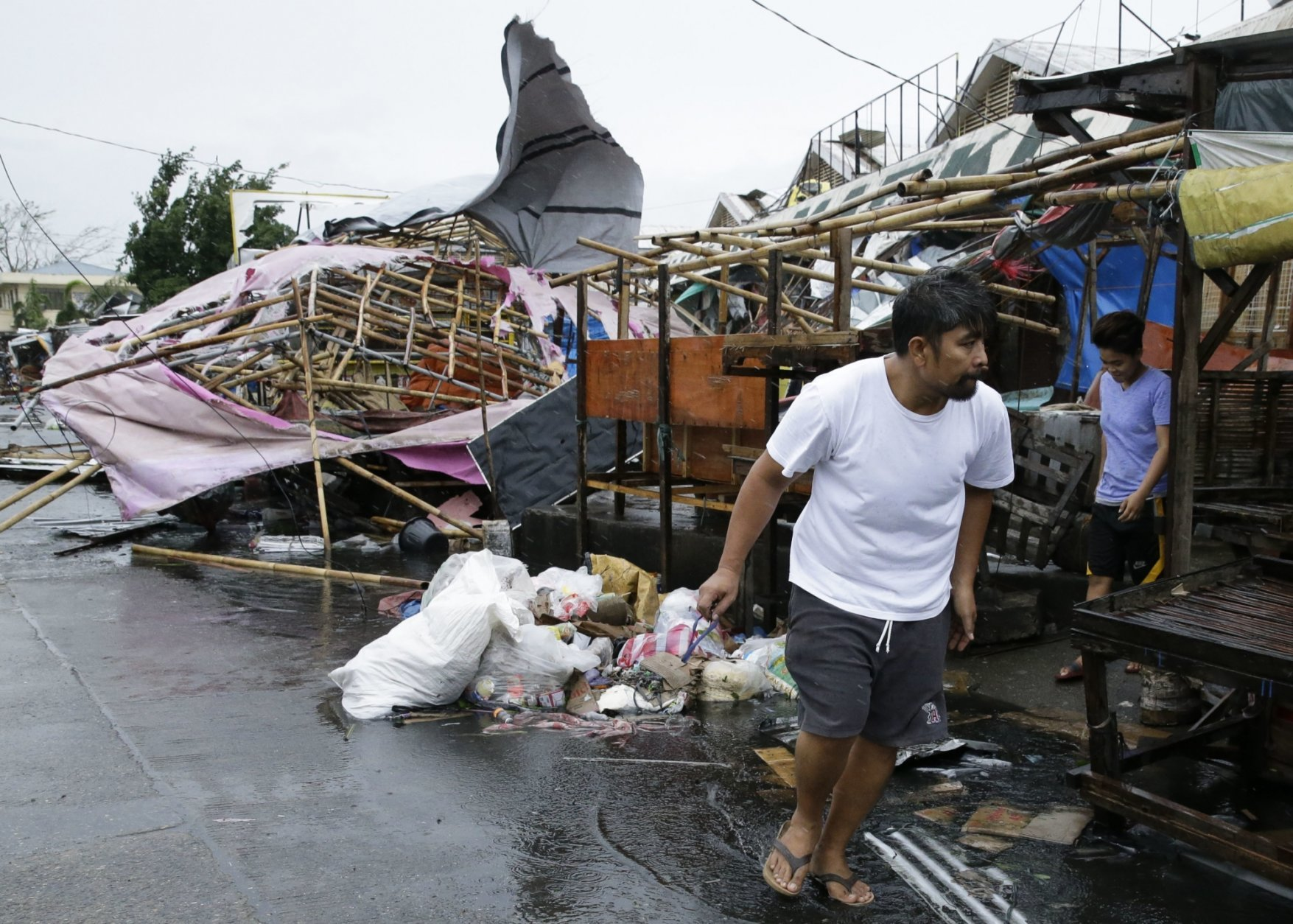 A resident walks past damaged stalls at a public market as Typhoon Mangkhut barreled across Tuguegarao city in Cagayan province, northeastern Philippines on Saturday, Sept. 15, 2018. The typhoon slammed into the Philippines northeastern coast early Saturday, it's ferocious winds and blinding rain ripping off tin roof sheets and knocking out power, and plowed through the agricultural region at the start of the onslaught. (AP Photo/Aaron Favila)