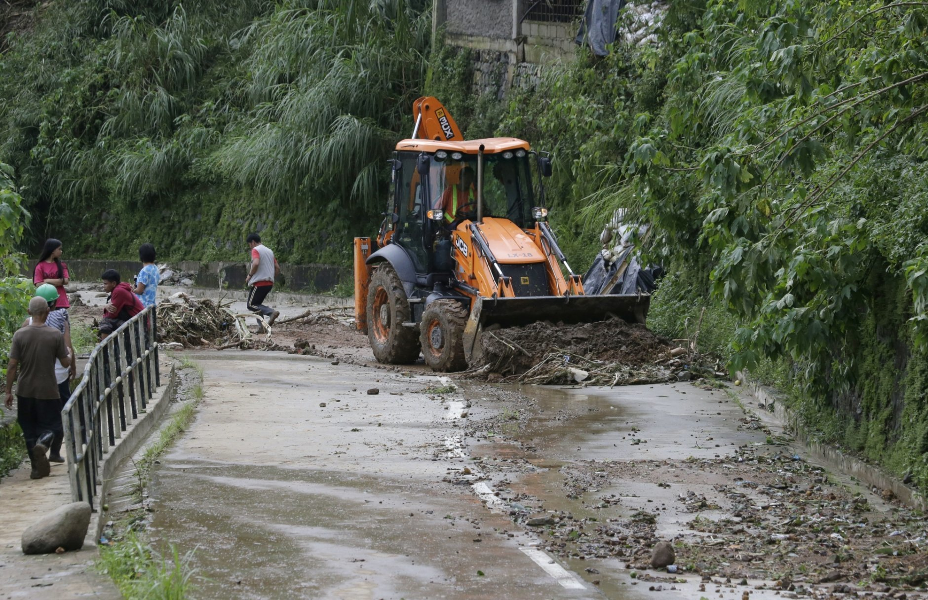 A bulldozer clears an area near the site of a landslide where victims are believed to still be buried after Typhoon Mangkhut barreled across Itogon, Benguet province, northern Philippines, Monday, Sept. 17, 2018. Itogon Mayor Victorio Palangdan said that at the height of the typhoon's onslaught Saturday afternoon, dozens of people, mostly miners and their families, rushed into an old three-story building in the village of Ucab. The building, a former mining bunkhouse that had been transformed into a chapel, was obliterated when part of a mountain slope collapsed. (AP Photo/Aaron Favila)