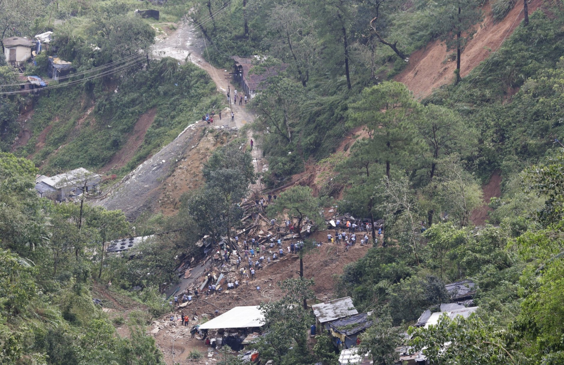 Rescuers dig on the site where victims were believed to have been buried by a landslide after Typhoon Mangkhut barreled across Itogon, Benguet province, northern Philippines, Monday, Sept. 17, 2018. Itogon Mayor Victorio Palangdan said that at the height of the typhoon's onslaught Saturday afternoon, dozens of people, mostly miners and their families, rushed into an old three-story building in the village of Ucab. The building, a former mining bunkhouse that had been transformed into a chapel, was obliterated when part of a mountain slope collapsed. (AP Photo/Aaron Favila)