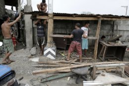 Residents rebuild a small roadside eatery after the old one was blown away by strong winds from Typhoon Mangkhut after it barreled across Tuguegarao city in Cagayan province, northeastern Philippines on Sunday, Sept. 16, 2018. Typhoon Mangkhut roared toward densely populated Hong Kong and southern China on Sunday after ravaging across the northern Philippines with ferocious winds and heavy rain causing landslides and collapsed houses. (AP Photo/Aaron Favila)