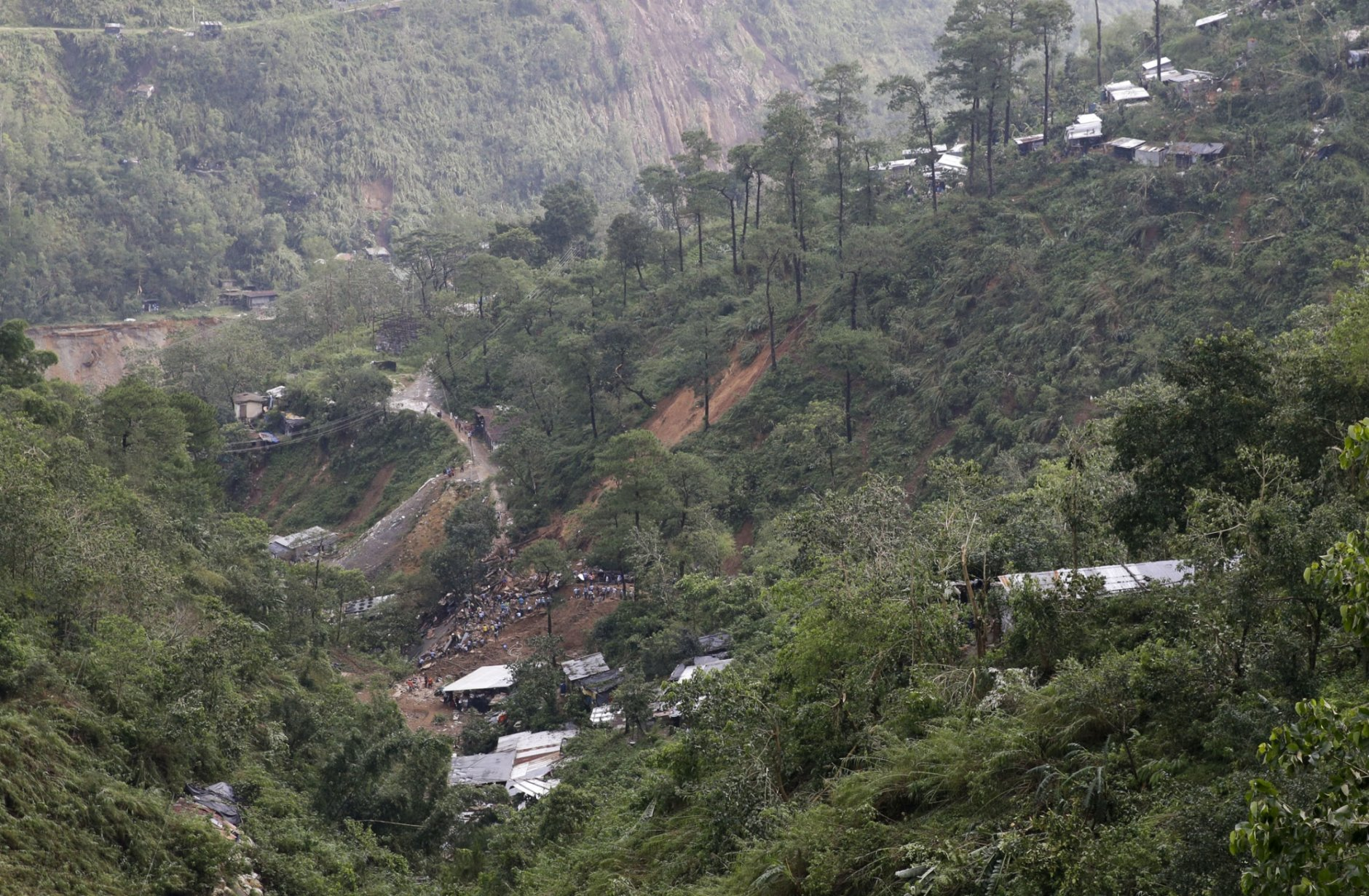 Rescuers at the site where victims were believed to have been buried by a landslide after Typhoon Mangkhut barreled across Itogon, Benguet province, northern Philippines, Monday, Sept. 17, 2018. Itogon Mayor Victorio Palangdan said that at the height of the typhoon's onslaught Saturday afternoon, dozens of people, mostly miners and their families, rushed into an old three-story building in the village of Ucab. The building, a former mining bunkhouse that had been transformed into a chapel, was obliterated when part of a mountain slope collapsed. (AP Photo/Aaron Favila)