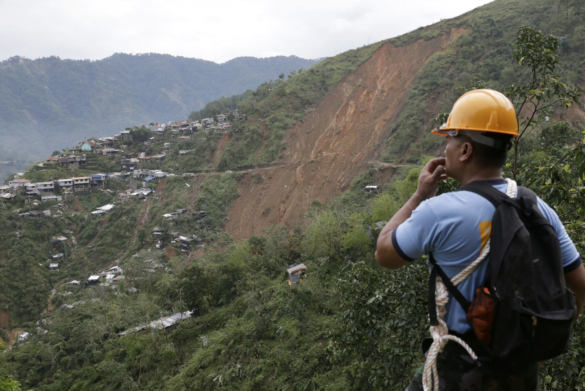 A rescuer looks at the site of a landslide where victims are believed to have been buried after Typhoon Mangkhut barreled across Itogon, Benguet province, northern Philippines, Monday, Sept. 17, 2018. Itogon Mayor Victorio Palangdan said that at the height of the typhoon's onslaught Saturday afternoon, dozens of people, mostly miners and their families, rushed into an old three-story building in the village of Ucab. The building, a former mining bunkhouse that had been transformed into a chapel, was obliterated when part of a mountain slope collapsed. (AP Photo/Aaron Favila)