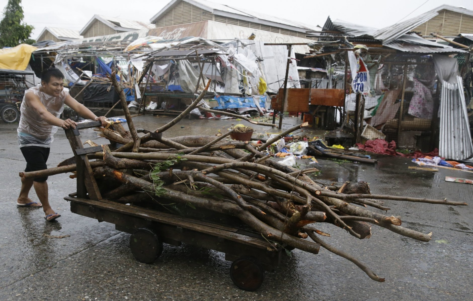 A resident pushes a cart full of wood as he passes market stalls destroyed by strong winds as Typhoon Mangkhut barreled across Tuguegrao city in Cagayan province, northeastern Philippines on Saturday, Sept. 15, 2018. The typhoon slammed into the Philippines northeastern coast early Saturday, it's ferocious winds and blinding rain ripping off tin roof sheets and knocking out power, and plowed through the agricultural region at the start of the onslaught. (AP Photo/Aaron Favila)