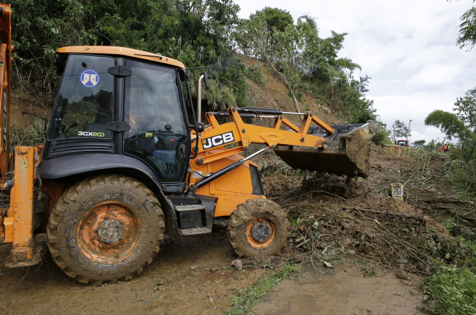 A truck works near the site where victims are believed to have been buried by a landslide after Typhoon Mangkhut barreled across Itogon, Benguet province, northern Philippines, Monday, Sept. 17, 2018. Itogon Mayor Victorio Palangdan said that at the height of the typhoon's onslaught Saturday afternoon, dozens of people, mostly miners and their families, rushed into an old three-story building in the village of Ucab. The building, a former mining bunkhouse that had been transformed into a chapel, was obliterated when part of a mountain slope collapsed. (AP Photo/Aaron Favila)