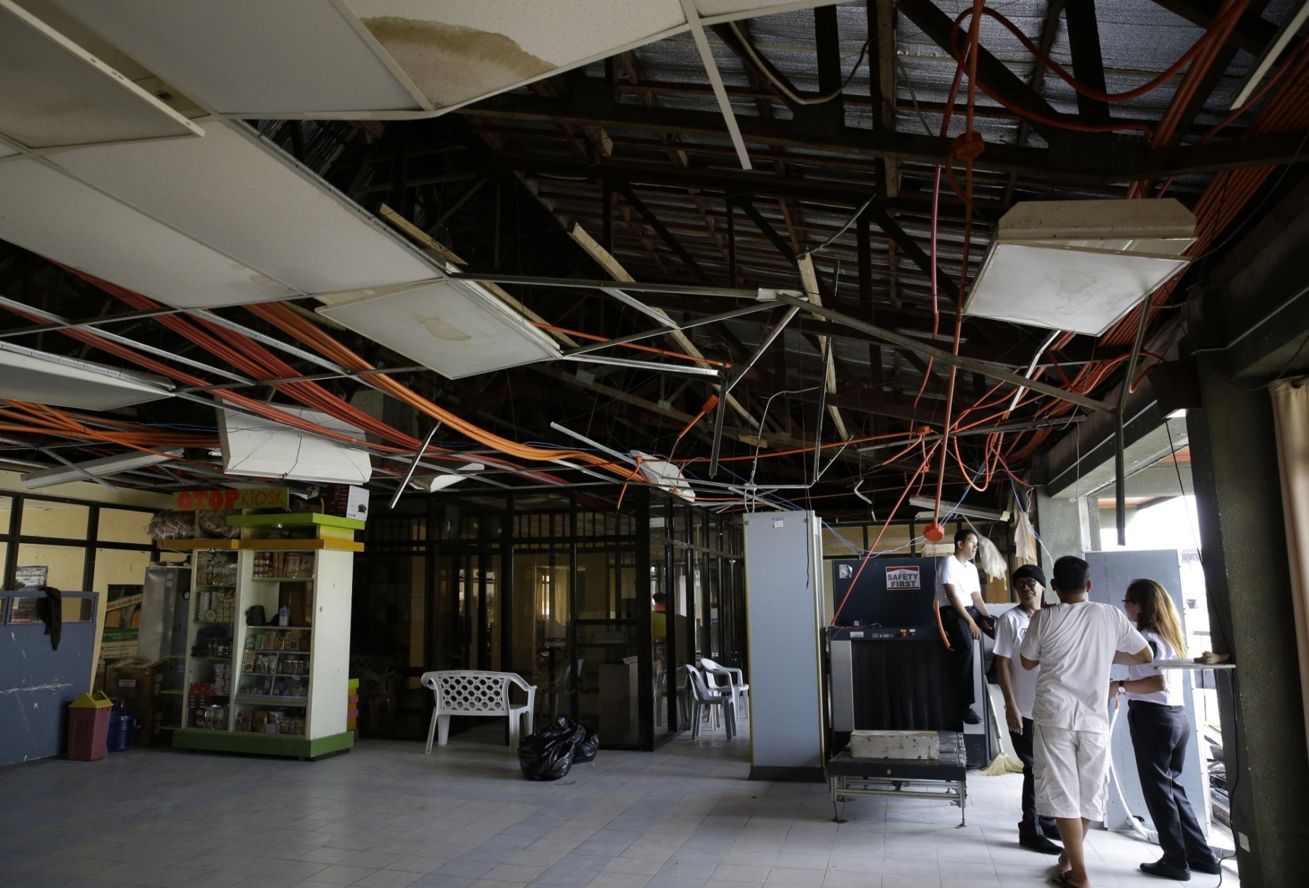 Workers wait inside the terminal of Tuguegarao's airport damaged due to strong winds from Typhoon Mangkhut in Cagayan province, northeastern Philippines on Sunday, Sept. 16, 2018. Typhoon Mangkhut roared toward densely populated Hong Kong and southern China on Sunday after ravaging across the northern Philippines with ferocious winds and heavy rain causing landslides and collapsed houses. (AP Photo/Aaron Favila)