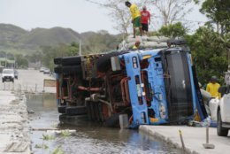 Workers transfer sacks of grains from a toppled truck that fell into an area where the road was being repaired in Cagayan province, northeastern Philippines on Sunday, Sept. 16, 2018. Driver Alvin Buelta said his truck fell after he failed to see the road repairs due to the high floods caused by Typhoon Mangkhut on Friday night. The typhoon roared toward densely populated Hong Kong and southern China on Sunday after ravaging across the northern Philippines with ferocious winds and heavy rain causing landslides and collapsed houses. (AP Photo/Aaron Favila)