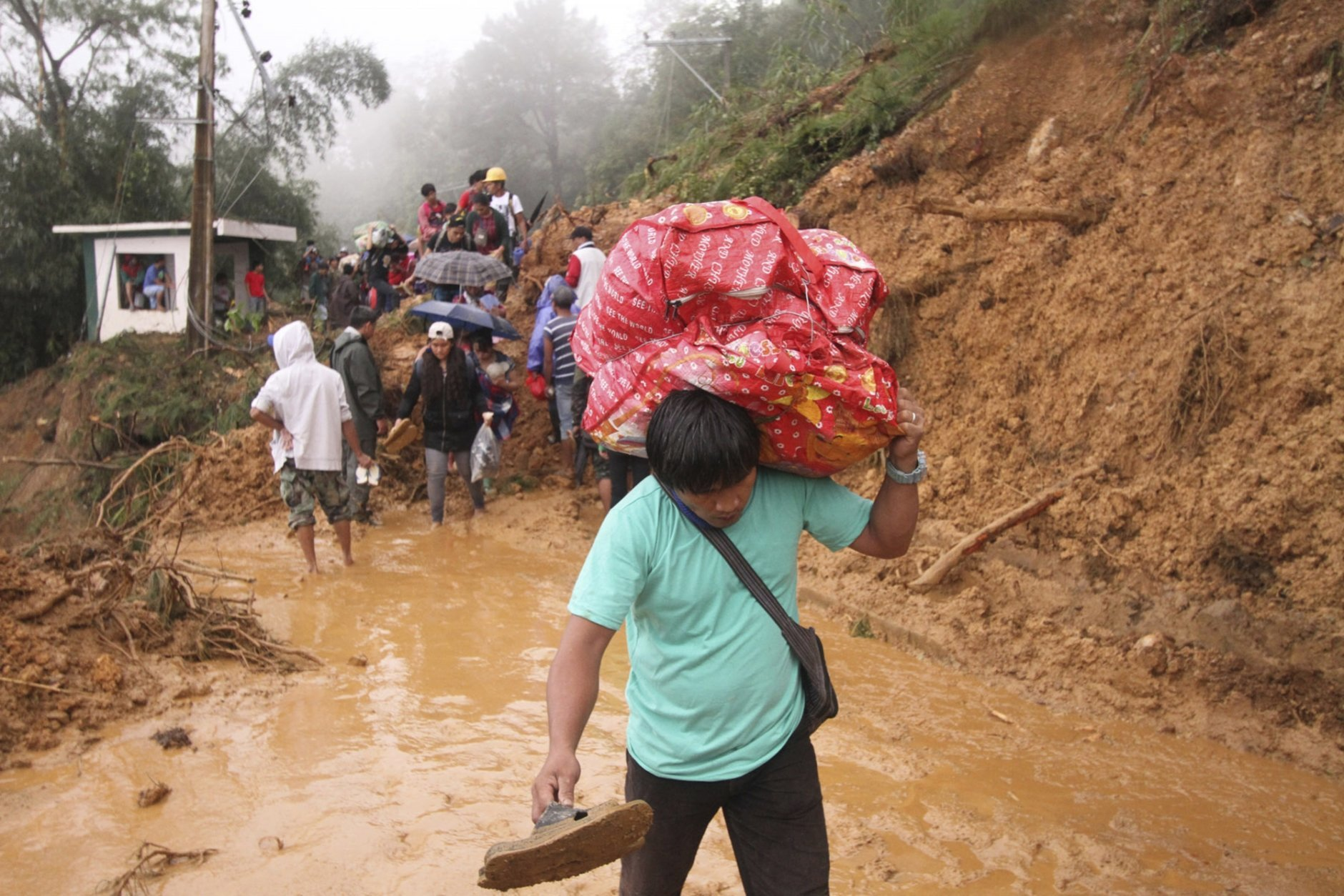 Families and relatives of miners in Itogon township, Benguet province in the northern Philippines, carry their belongings as they evacuate following landslides which were triggered by Typhoon Mangkhut burying an unknown number of miners and isolating the township Sunday, Sept. 16, 2018. Typhoon Mangkhut barreled into southern China on Sunday after lashing the northern Philippines with strong winds and heavy rain that left more than dozens dead from landslides and drownings. (AP Photo/Jayjay Landingin)